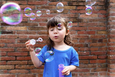 Portrait of little girl with eyes closed blowing soap bubbles in front of brick wall - GEMF03603