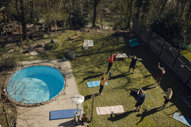 Group of friends doing workout together in garden - GUSF03595