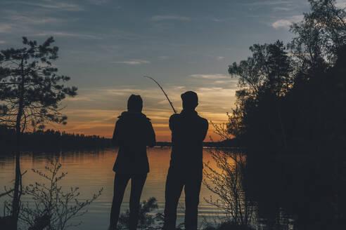 Couple standing at lake, fishing in lake at sunset - GUSF03700