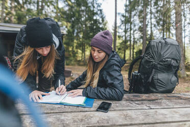 Young woman backpacking in Sweden, signing at camping ground - GUSF03715