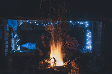 Friends sitting at campfire, staying over outdoors - GUSF03730