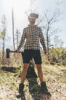 Young man gaming with VR glasses in the forest, holding axe - GUSF03739