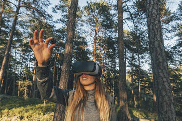 Young woman using VR goggles in nature, looking at pine cone - GUSF03766
