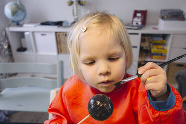 Portrait of little girl painting ball at home - JOSEF00321