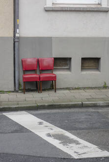 Two red old chairs standing side by side on pavement - JOSEF00327