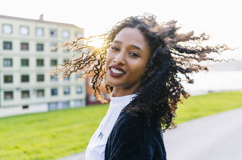 Portrait of young woman with ringlets tossing her hair at backlight - DGOF00929