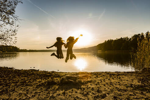 Friends jumping in mid-air while enjoying at lakeshore during sunset - OJF00392