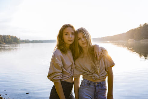 Portrait of friends standing with arm around against lake during sunset - OJF00395