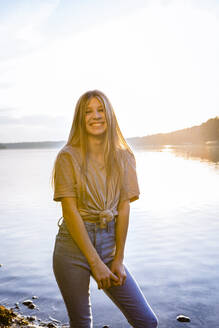 Portrait of happy girl standing at lakeshore against sky during sunset - OJF00398
