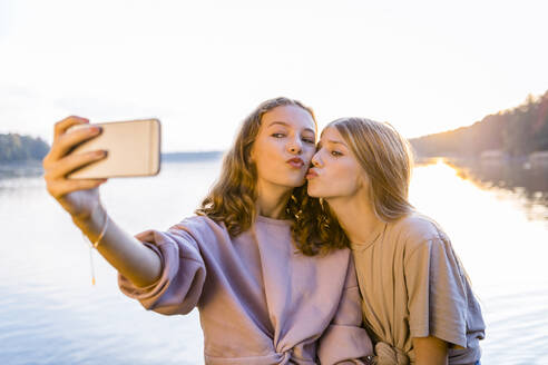 Friends puckering lips while taking selfie on smart phone against lake - OJF00401