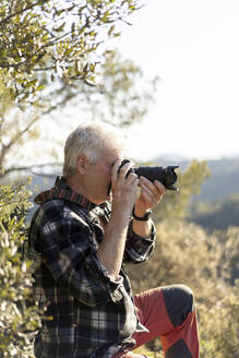 Senior man photographing in nature - AFVF06128