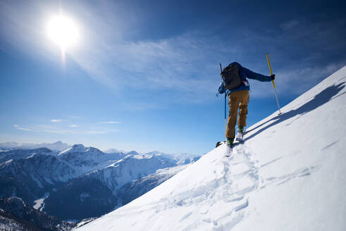 Ski touring uphill with a mountain backdrop - CAVF79683