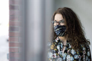 Woman wearing protective mask at window glass - FLLF00451