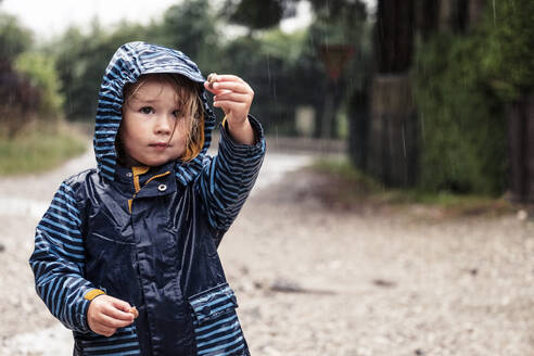 Portrait of little girl with snails in her hands standing in the rain - WFF00373