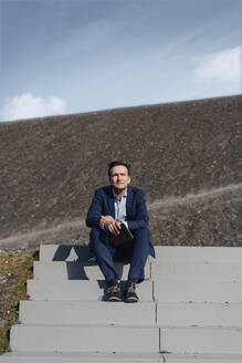 Mature businessman sitting on stairs on a disused mine tip holding tablet - JOSEF00377