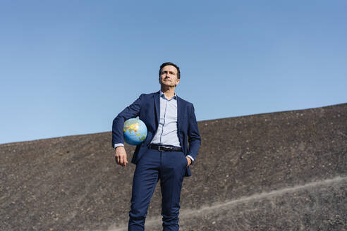Mature businessman holding a globe on a disused mine tip - JOSEF00383