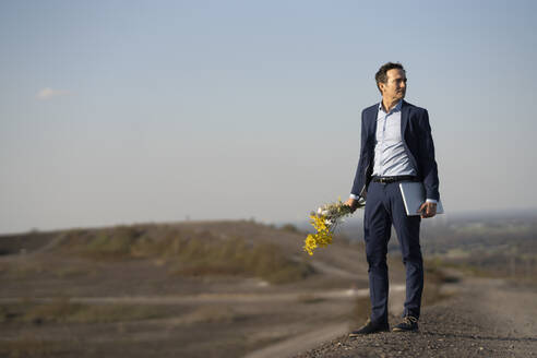 Mature businessman holding bunch of flowers and laptop on a disused mine tip - JOSEF00431