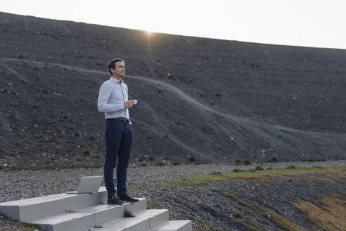 Mature businessman standing on stairs on a disused mine tip having a coffee break - JOSEF00455