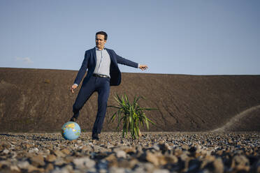 Mature businessman playing soccer with a globe on a disused mine tip - JOSEF00464