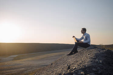 Mature businessman using laptop on a disused mine tip at sunset - JOSEF00476