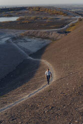 Mature businessman walking on a disused mine tip - JOSEF00482