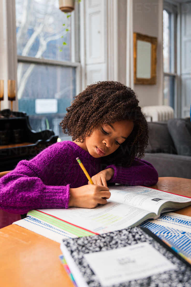 Girl Doing Homework While Sitting At Table In Living Room Stockphoto
