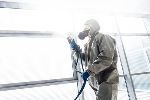 Cleaning staff desinfecting against contageous virus, wearing protective clothing - JCMF00598