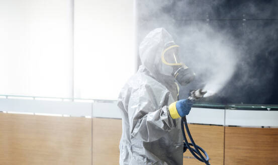 Cleaning staff desinfecting hospital against contageous virus, wearing protective clothing - JCMF00613