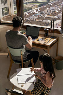 Father working on laptop while his daughter doing homework - ERRF03526