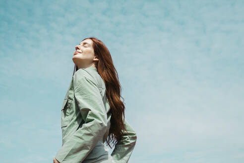 Portrait of redheaded young woman with eyes closed against sky - AFVF06144