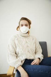 Portrait of blond woman wearing FFP2 mask at home - FSF01031
