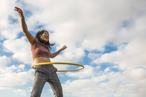 Happy woman playing with hula hoop outdoors - XLGF00073