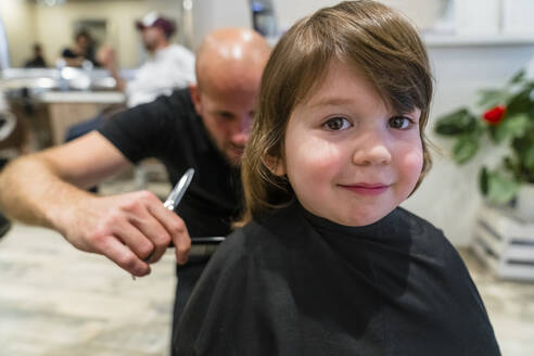 Portrait of smiling little girl getting haircut - MGIF00904