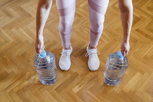 High angle view of woman performing weight training with water bottles at home - JCMF00652