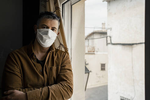 Man wearing protective mask and looking out of the window - RCPF00232