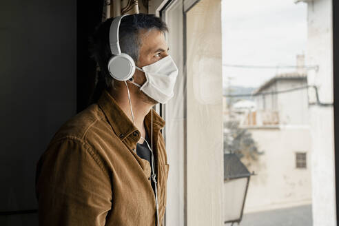 Man wearing protective mask and white headphones looking out of the window - RCPF00235