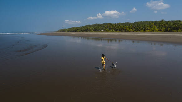 Carefree young woman taking her dog for a walk at the beach, Costa Rica - AMUF00091