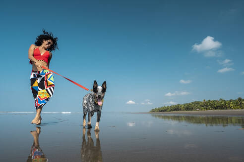 Carefree young woman taking her dog for a walk at the beach, Costa Rica - AMUF00094
