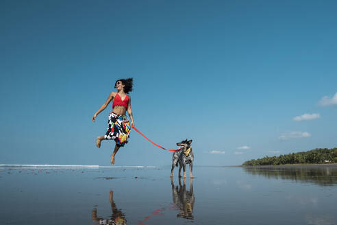 Carefree young woman taking her dog for a walk at the beach, Costa Rica - AMUF00097