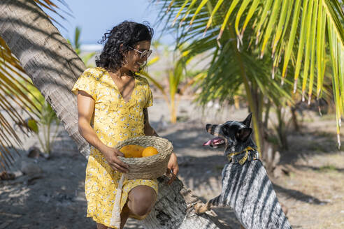 Young woman holding a fruit basket at the beach with her dog, Costa Rica - AMUF00100