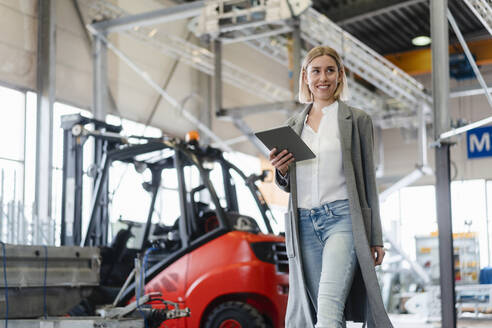 Smiling young woman holding tablet walking in a factory - DIGF09912