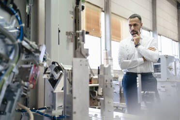 Businessman looking at modern machine in a factory - DIGF09948