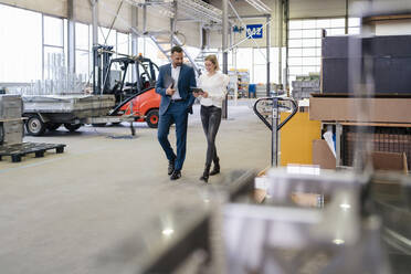 Businessman and young woman with tablet walking and talking in a factory - DIGF09951