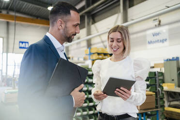 Businessman and young woman with tablet talking in a factory - DIGF09954