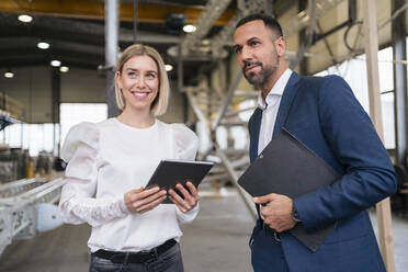 Businessman and smiling young woman with tablet in a factory - DIGF09957
