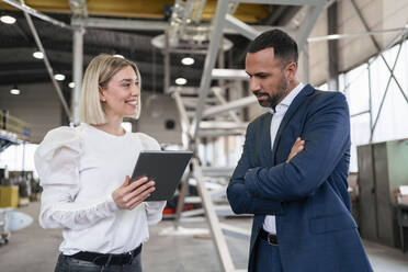 Businessman and young woman with tablet talking in a factory - DIGF09960