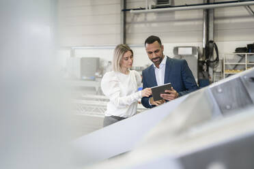 Businessman with tablet and young woman talking in a factory - DIGF09966