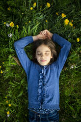 Portrait of girl with eyes closed relaxing on a meadow in spring - LVF08852