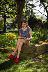 Smiling girl sitting in garden looking at digital tablet - LVF08859