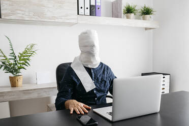 Man working at home with his head covered in toilet paper - JRFF04398